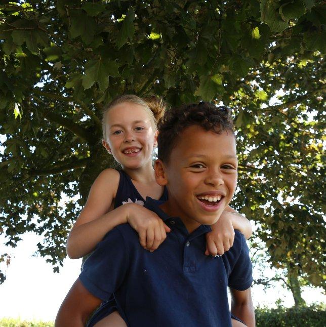 Klein kind zittend op rug van groot kind beide lachend
