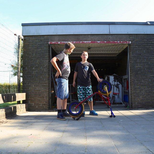 Twee kinderen buiten voor een garage met een kapotte fiets