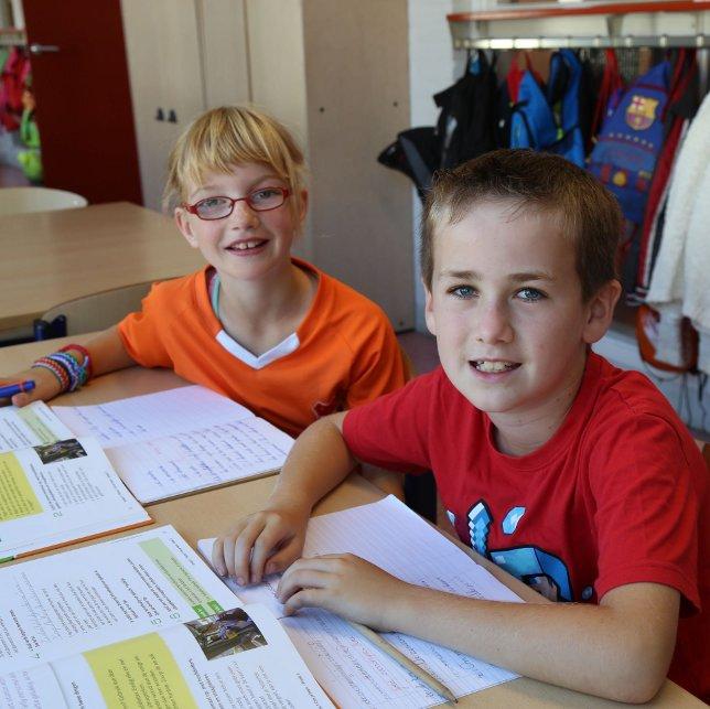 Twee kinderen aan het werk met schoolboeken